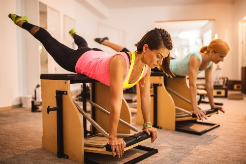 Athletic women exercising on Pilates stability chairs in health club