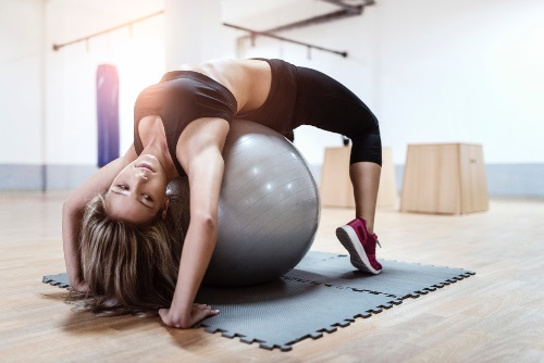 Young Woman Doing Pilates Pose With Ball