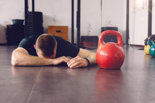 man falls at the gym and feels embarrassed