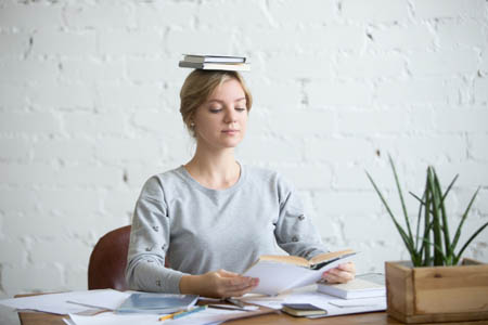 woman with good posture balancing book on head