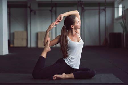 Young Woman Doing Yoga King Pigeon Pose